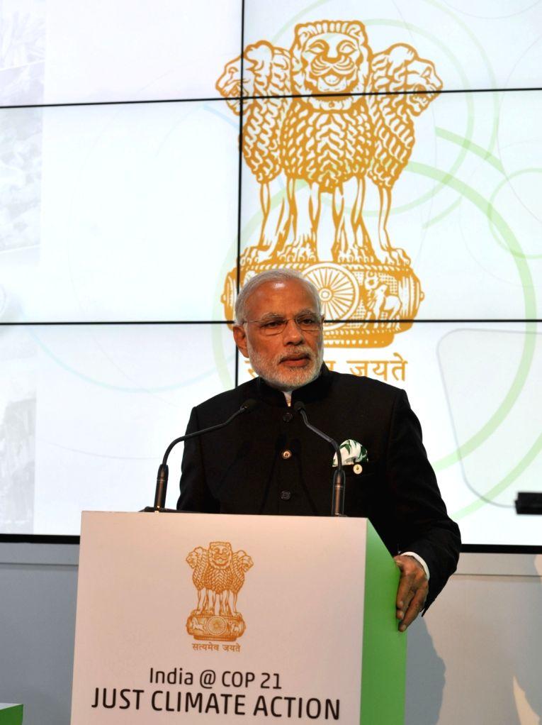 Caption : Paris: Prime Minister Narendra Modi addresses at the inauguration of the India Pavilion, at COP21 Summit, in Paris, France on Nov 30, 2015. - Narendra Modi