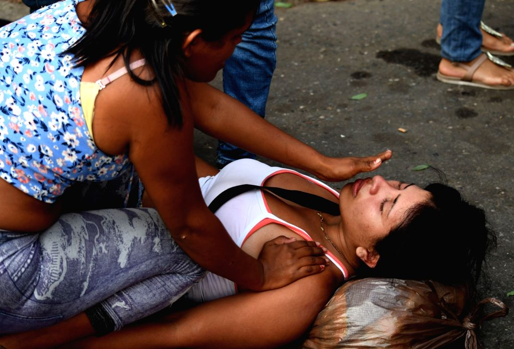 CARABOBO, March 29, 2018 - A woman faints as relatives wait for information after an alleged fire at a Venezuelan police station, in Valencia, Carabobo state, Venezuela, on March 28, 2018. A prison ...