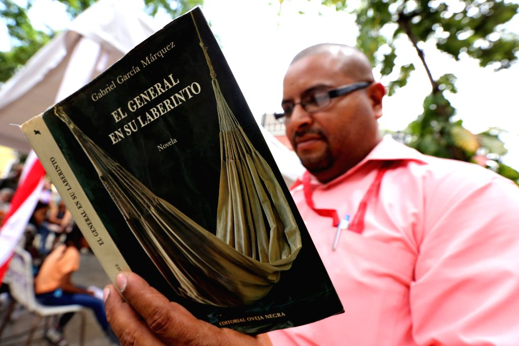 """A man reads the book """"The General in his Labyrinth"""" by late Colombian writer Gabriel Garcia Marquez, at Bolivar Square in Caracas, Venezuela, on April ..."""