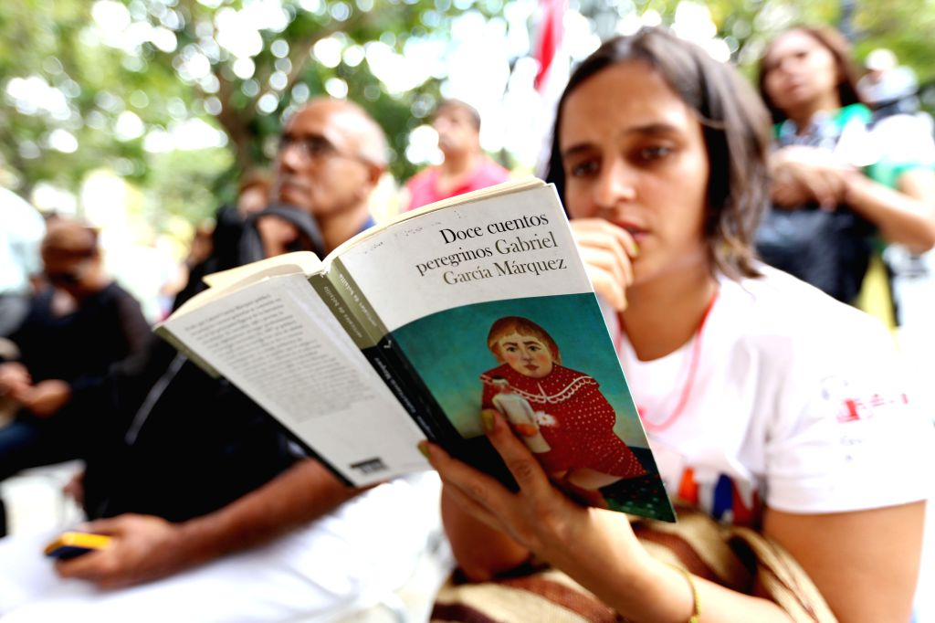 """A woman reads the book """"Strange Pilgrims: Twelve Stories"""" by late Colombian writer Gabriel Garcia Marquez, at Bolivar Square in Caracas, Venezuela, on ..."""