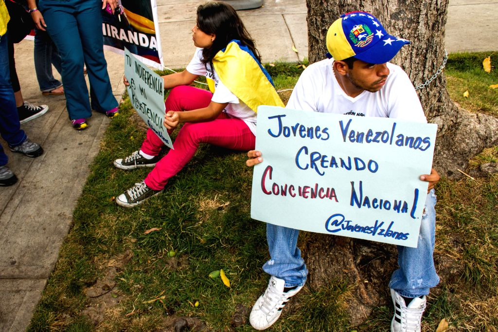 Supporters of Leopoldo Lopez hold banners with slogans to support Venezuelean opposition leader on his 43rd birthday in Palos Grandes, Caracas, Venezuela, April ...