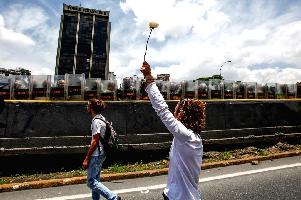CARACAS, May 7, 2017 - A demonstrator holds a white rose in front of members of the National Bolivarian Police during a rally organized by female supporters of the opposition in Caracas, Venezuela, ...
