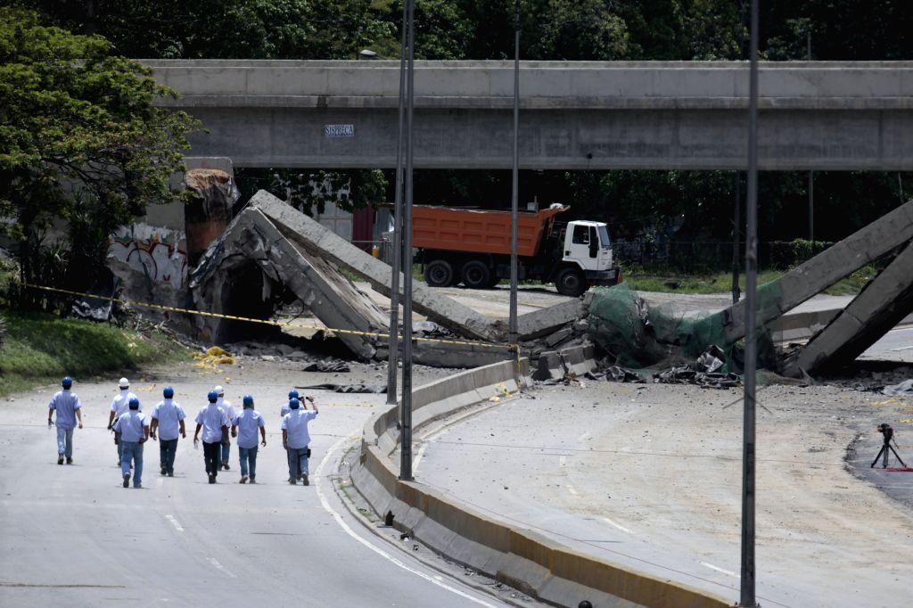 Workers walk towards the Santa Cecilia Bridge after its demolition in a controlled explosion on the Francisco Fajardo Highway in Caracas, capital of Venezuela, ...