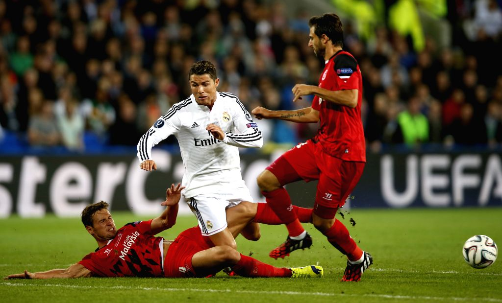 Cristiano Ronaldo(C) of Real Madrid is tackled by Grzegorz Krychowiak of Sevilla during the UEFA Super Cup match between Real Madrid and Sevilla at Cardiff City ...