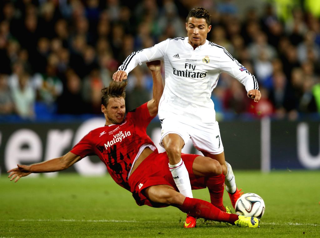 Cristiano Ronaldo(R) of Real Madrid is tackled by Grzegorz Krychowiak of Sevilla during the UEFA Super Cup match between Real Madrid and Sevilla at Cardiff City ...