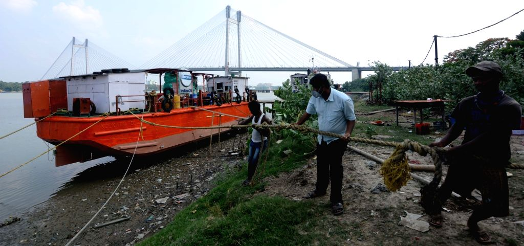 Cargo barge being tied up the side off on the banks of the Ganges for preparation of  the fear of Super Cyclone Yaas in Kolkata 23 May, 2021.