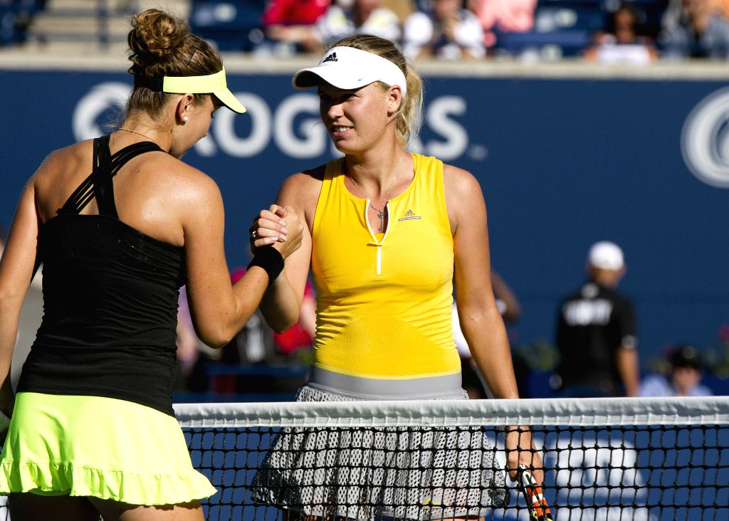 Caroline Wozniacki (R) of Denmark shakes hands with Belinda Bencic of Switzerland after their women's singles 2nd round match at the 2015 Rogers Cup in Toronto, ...