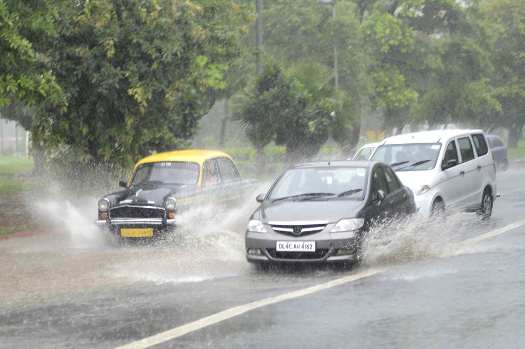 Cars splash water as they travel on flooded streets of New Delhi on Sept 11, 2014.