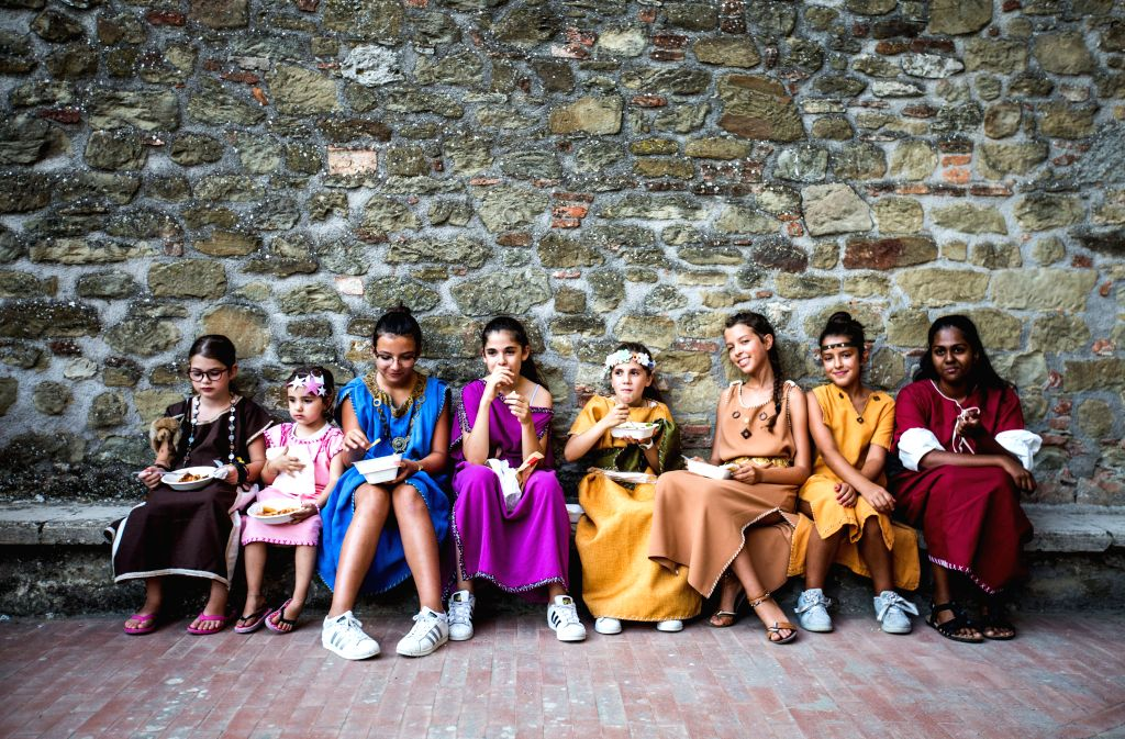 CASTEL RIGONE, Aug. 5, 2018 - Girls in costumes have dinner in Castel Rigone, Italy, on Aug. 3, 2018. The Festival of the Barbarians, an event to commemorate the founding of the town, was held in ...
