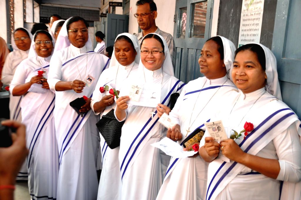 Catholic nuns stand in a queue waiting to cast their vote with rose in their hand during the fifth phase of Lok Sabha election in Ranchi, Jharkhand on April 17, 2014.
