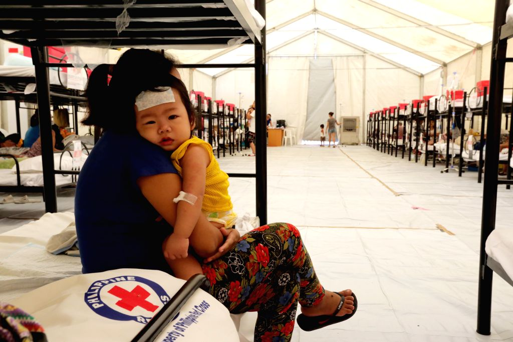 CAVITE PROVINCE, Aug. 13, 2019 - A mother attends to her sick child as they rest with other dengue patients at a Dengue Emergency Medical Unit set up by the Philippine Red Cross in Cavite Province, ...
