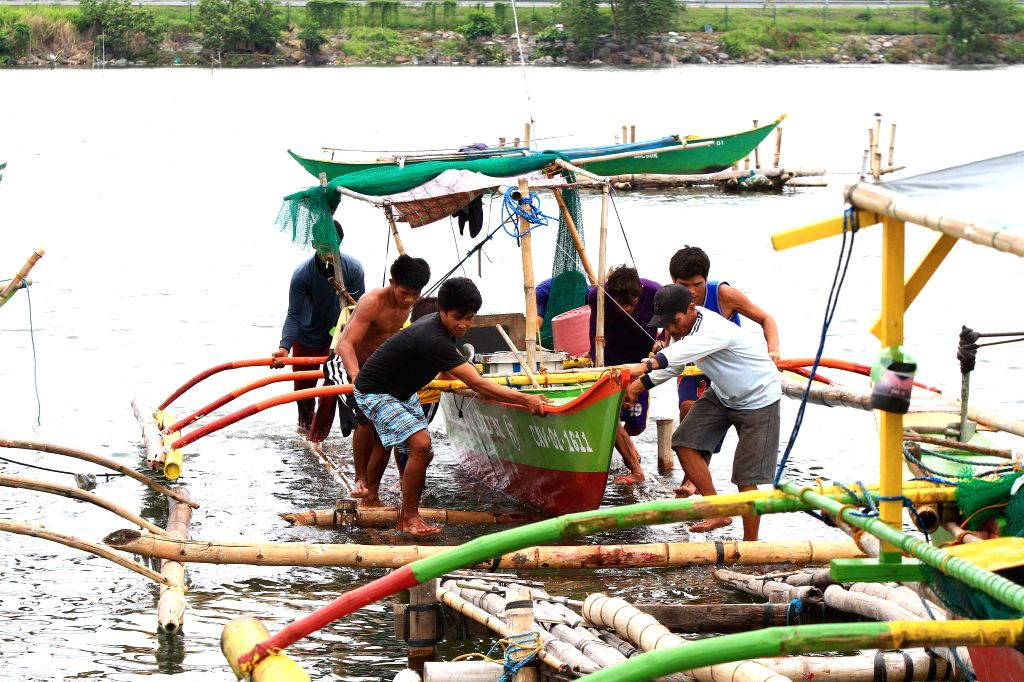 Fishermen secure their boat in Cavite Province, the Philippines, July 15, 2014. People prepared for the typhoon Rammasun as the first major storm of the ...