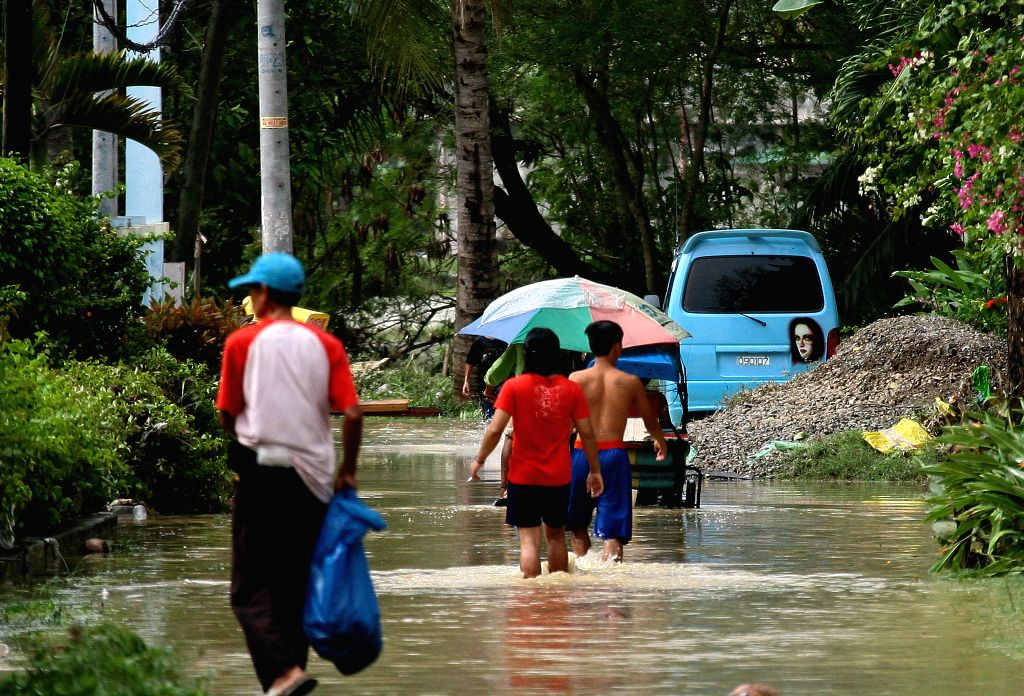 Residents walk in flood brought by Tropical Storm Jangmi in Cebu Province, the Philippines, Dec. 30, 2014. At least six people died in flood-triggered incidents and ...