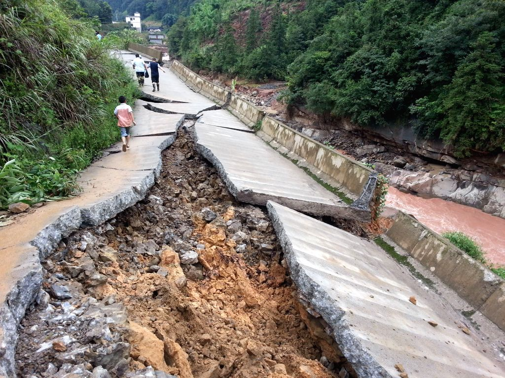 Cell phone photo taken on Aug. 18, 2015 shows a road damaged in flood caused by rainstorm in Baila Miao Township of Xuyong County in Luzhou City, southwest China's ...