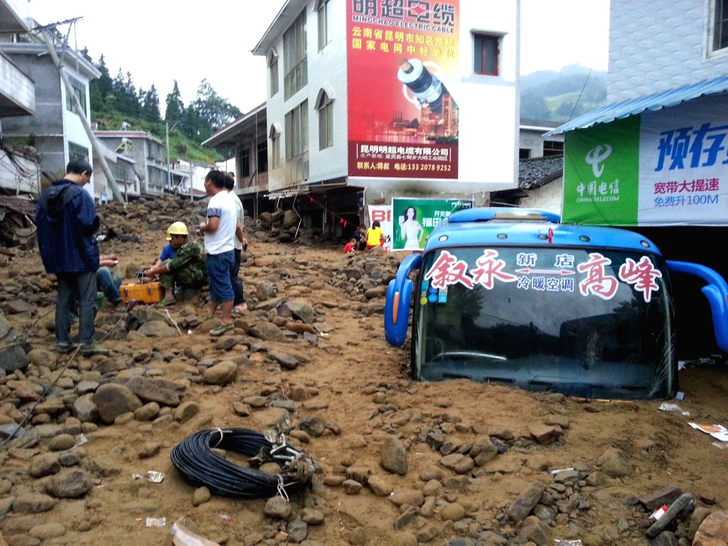 Cell phone photo taken on Aug. 18, 2015 shows a bus buried in mudslides at Gaofeng Village in Baila Miao Township of Xuyong County in Luzhou City, southwest China's ...
