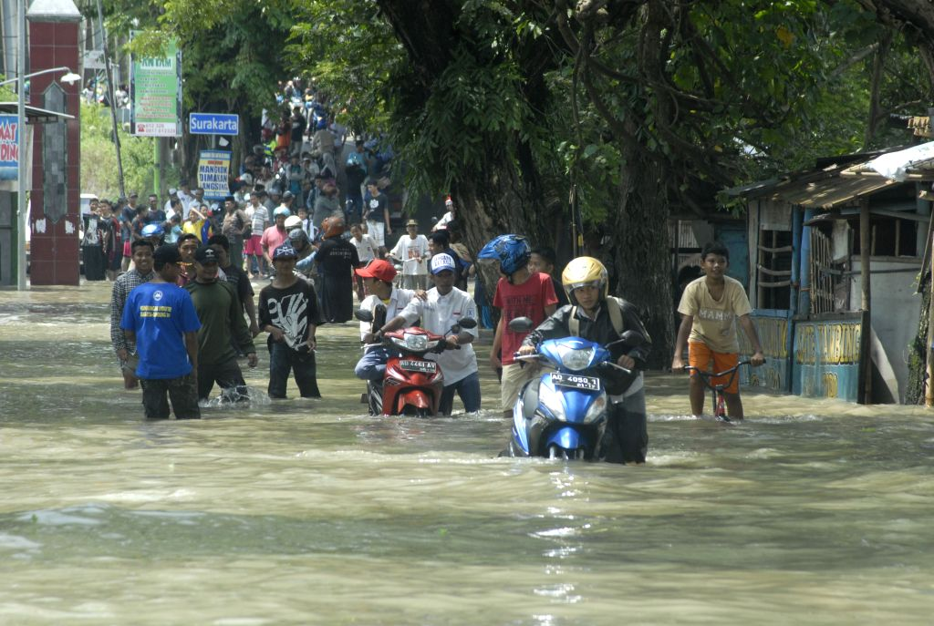 CETRAL JAVA, Nov. 29, 2016 - People wade through a flooded street at Sukoharjo in Central Java, Indonesia, Nov. 29, 2016. Flood has hit a number of areas in Sukoharjo, Solo and Karanganyar in Central ...