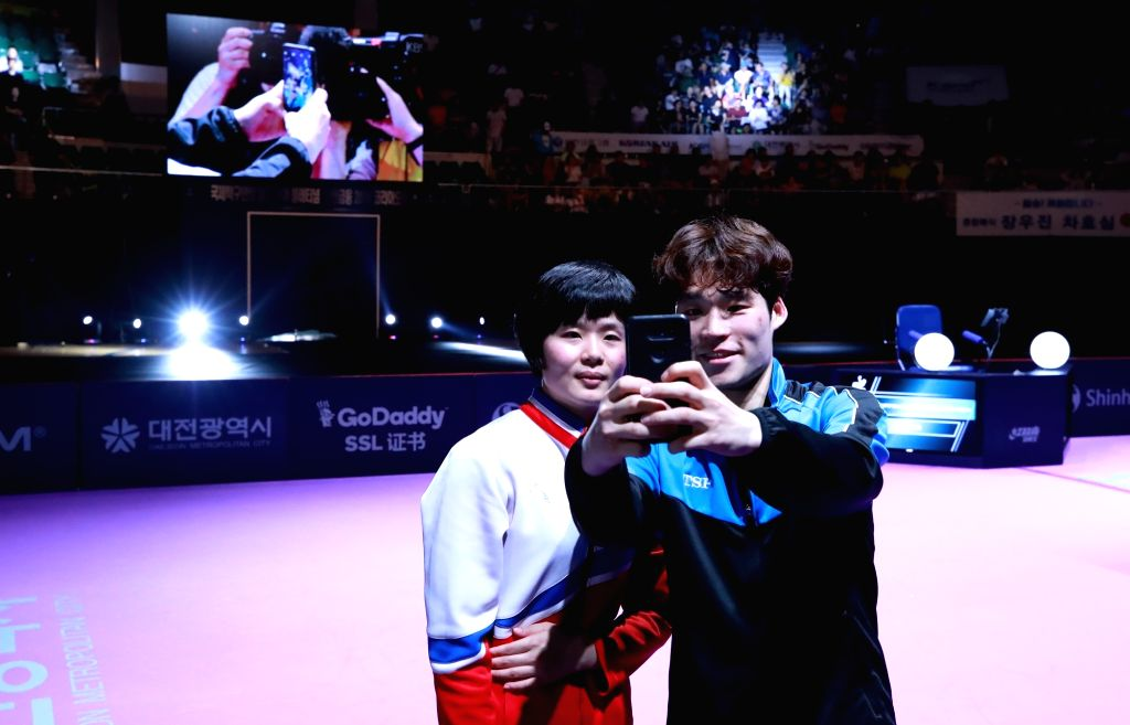Cha Hyo-sim of North Korea (L) and Jang Woo-jin of South Korea take a selfie together after capturing the mixed doubles table tennis title at the International Table Tennis Federation (ITTF) ...