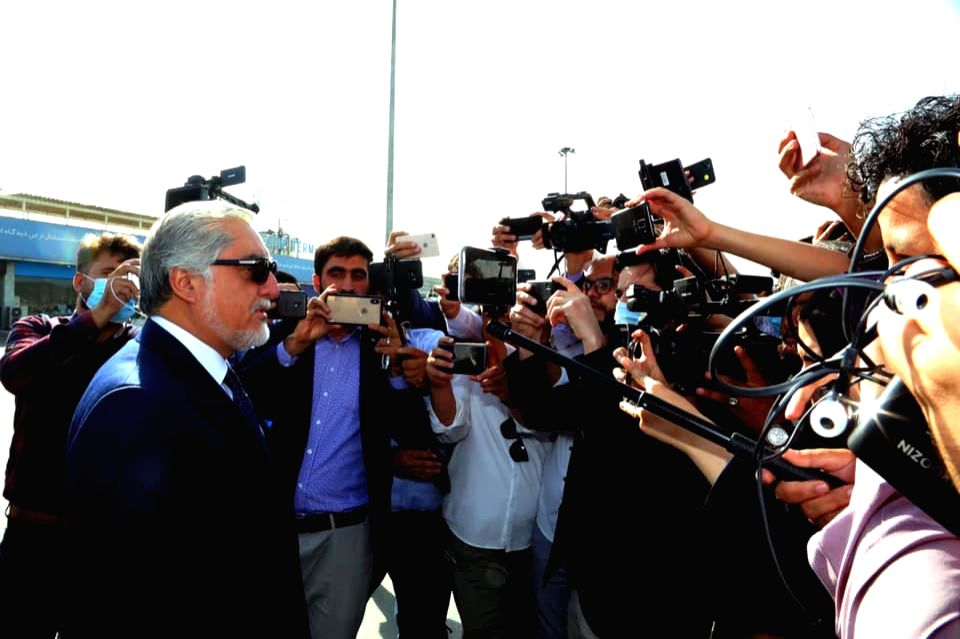 Chairman of the High Council for National Reconciliation Abdullah Abdullah (L, front) talks with the press before embarking the plane for Doha at Kabul International ...