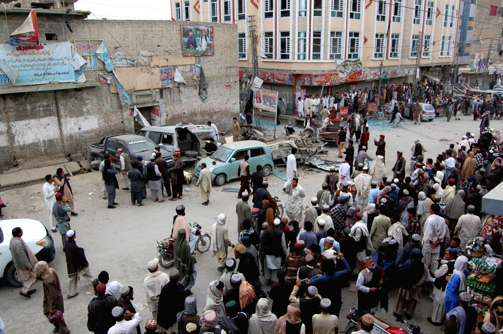 People gather at the blast site in Chaman district of Balochistan province, Pakistan, Feb. 22, 2015. An eight-year-old boy was killed and eight others injured when a ...