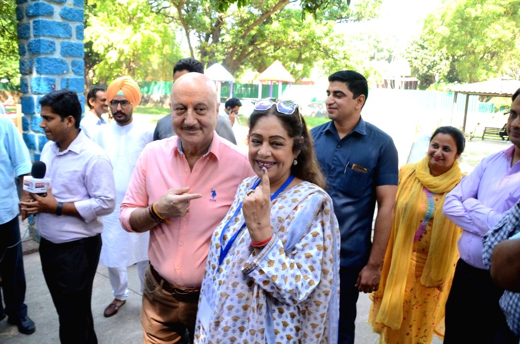 Chandigarh: Actors Kirron Kher and Anupam Kher show their his forefinger marked with indelible ink after casting vote during the seventh and the last phase of 2019 Lok Sabha Elections at a polling booth in Chandigarh on May 19, 2019. Kirron is sittin - Kirron Kher and Anupam Kher