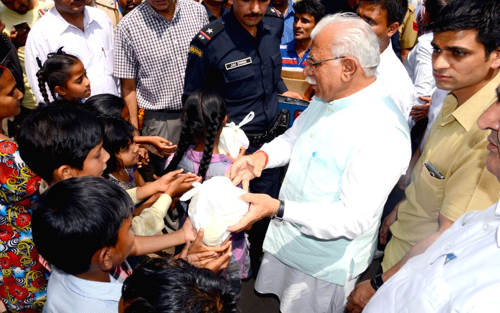 Haryana Chief Minister Manohar Lal Khattar distributes fruits to children on his birthday in Chandigarh on May 5, 2015. - Manohar Lal Khattar