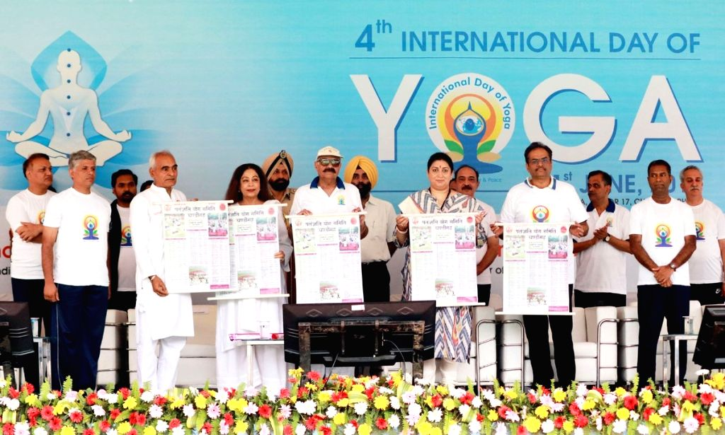 Chandigarh: Punjab Governor V.P. Singh Badnore and Union Textile Minister Smriti Z Irani release a calendar on the Fourth International Yoga Day, in Chandigarh on June 21, 2018. (Photo: IANS/PIB) - Smriti Z Irani and P. Singh Badnore