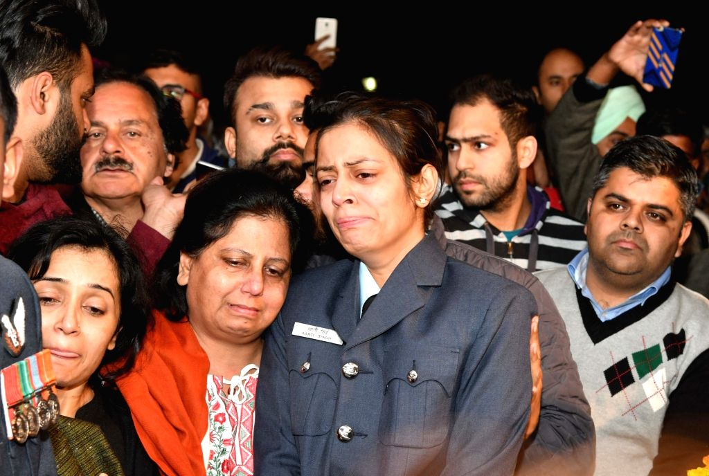 Chandigarh: Squadron Leader Aarti Vashisht, wife of Squadron leader Siddharth Vashisht - one of the pilots of the Mi-17 helicopter that crashed in Jammu and Kashmir's Budgam, reacts as his coffin arrives in Chandigarh on Feb 28, 2019. (Photo: IANS)