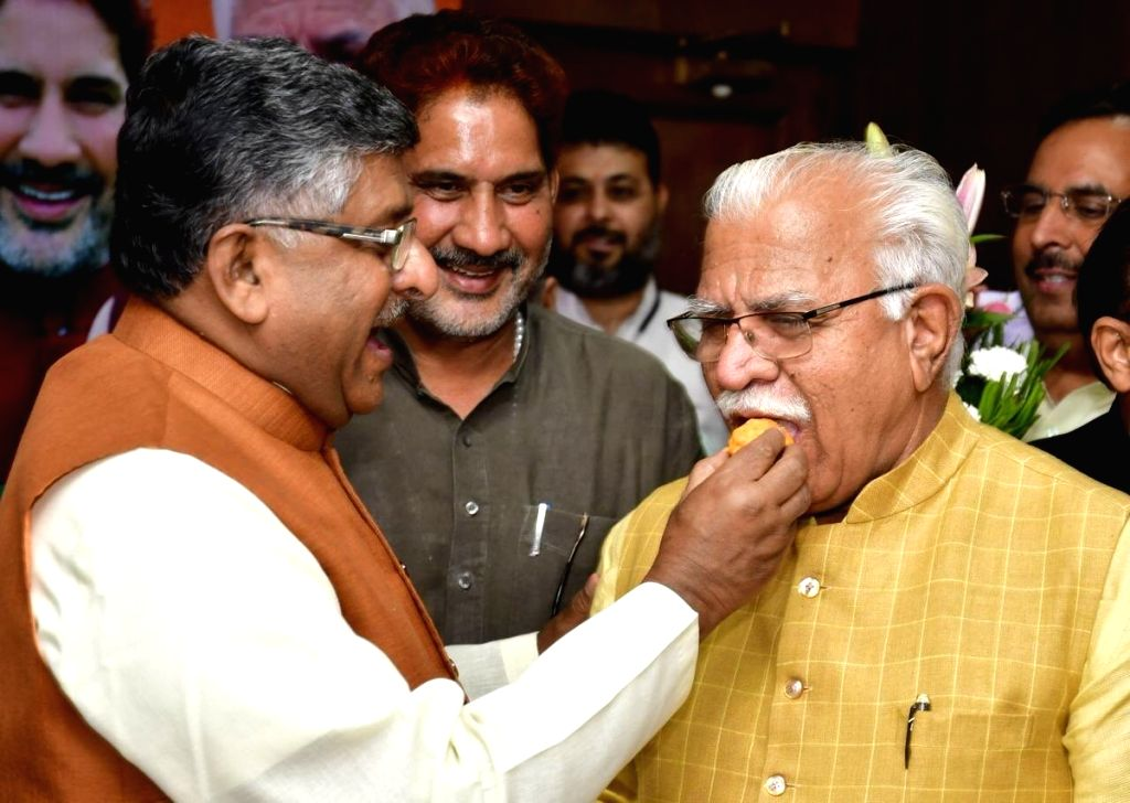 Chandigarh: Union Minister Ravi Shankar Prasad fetches sweet to incumbent Haryana Chief Minister Manohar Lal Khattar after the latter was elected as the leader of the Bharatiya Janata Party (BJP) Legislature Party, at the party office in Chandigarh o - Ravi Shankar Prasad and Manohar Lal Khattar