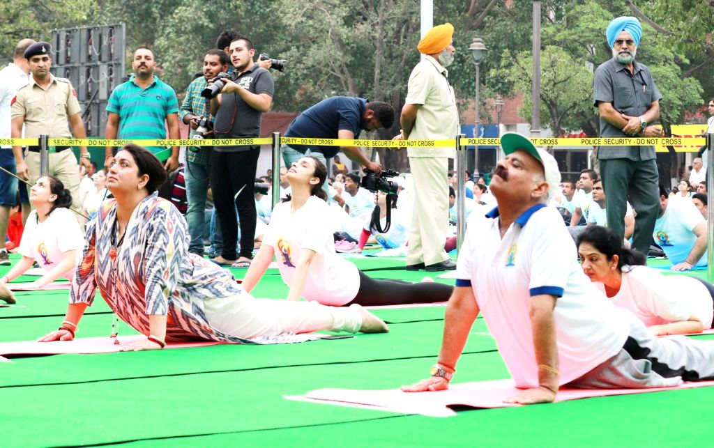 Chandigarh: Union Textile Minister Smriti Irani and Punjab and Chandigarh Administrator V.P. Singh Badnore practices yoga 'asanas' (postures) during Fourth International Yoga Day celebrations, in Chandigarh on June 21, 2018. (Photo: IANS/PIB) - Smriti Irani and P. Singh Badnore