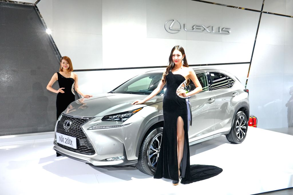 Two models present a new Lexus NX car at the 11th China International Automobile Expo in Changchun, capital of northeast China's Jilin Province, July 11, 2014. ...