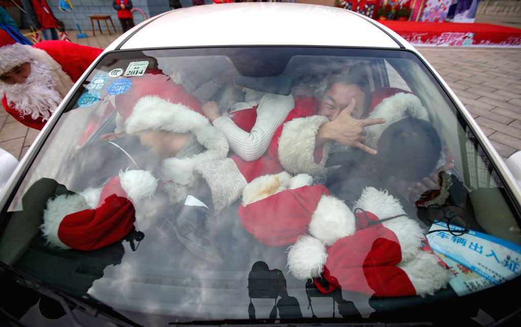 Participants dressed like Santa Claus are crammed into a car during a car loading game in the Colorful World Park of Changsha, capital of central China's Hunan ...