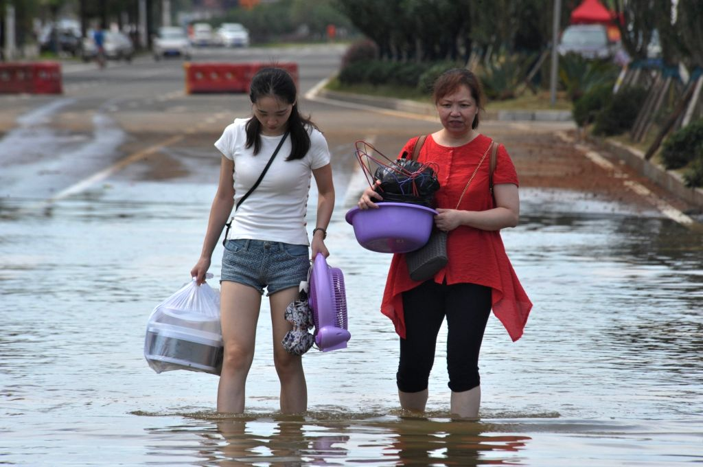 CHANGSHA, July 5, 2017 - Residents walk through a submerged road in the urban area of Changsha, capital of central China's Hunan Province, July 5, 2017. Rain-triggered floods have killed 27 people ...