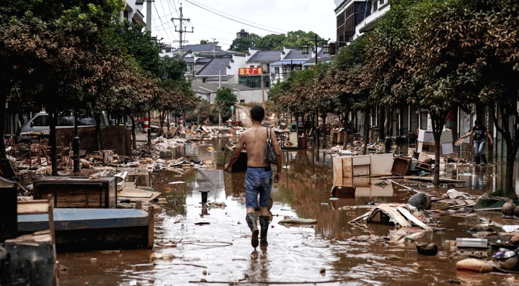 CHANGSHA, July 6, 2017 - A resident walks on a flood-whipped road in Changsha County, central China's Hunan Province, July 6, 2017. As rain-triggered flood recedes, residents here start rebuilding ...