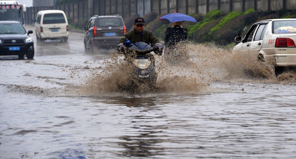 A man rides on a waterlogged road in Changsha, capital of central China's Hunan Province, March 23, 2015. Due to heavy rain, many areas in Changsha suffered ...