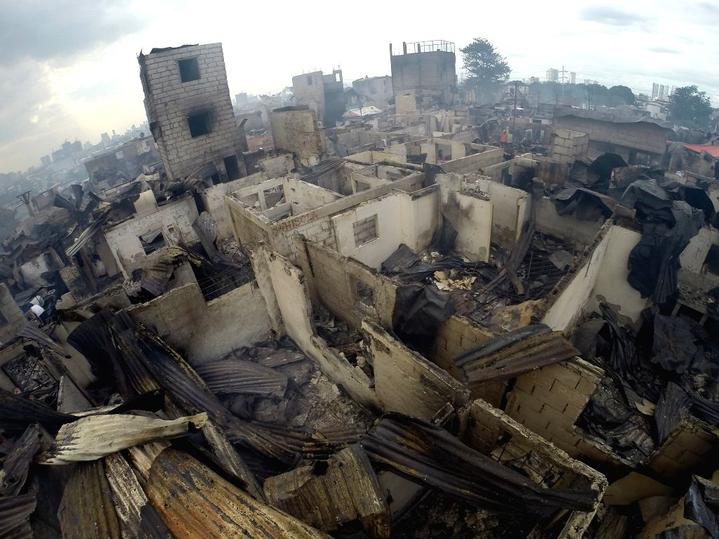 Charred homes are seen after a fire at a residential area in Mandaluyong City, the Philippines, Nov. 14, 2016. 2 people died while more than 6,000 people ...