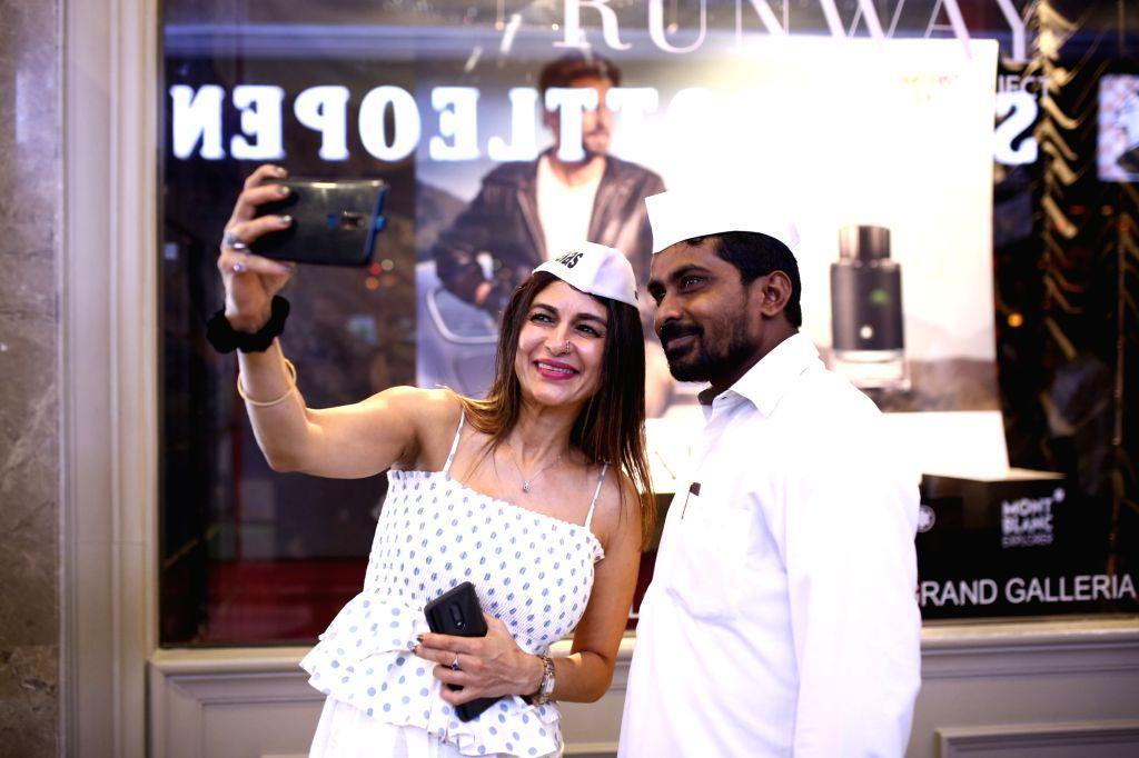 Chef Anaida Parvaneh sharing a moment with fellow Dabbawalas in Mumbai.