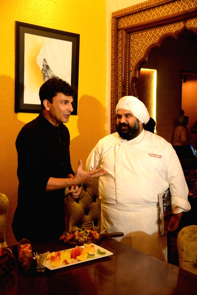 Chef Vikas Khanna interacts with a cook during his visit to a restaurant in Mumbai's Andheri on July 28, 2019. - Vikas Khanna