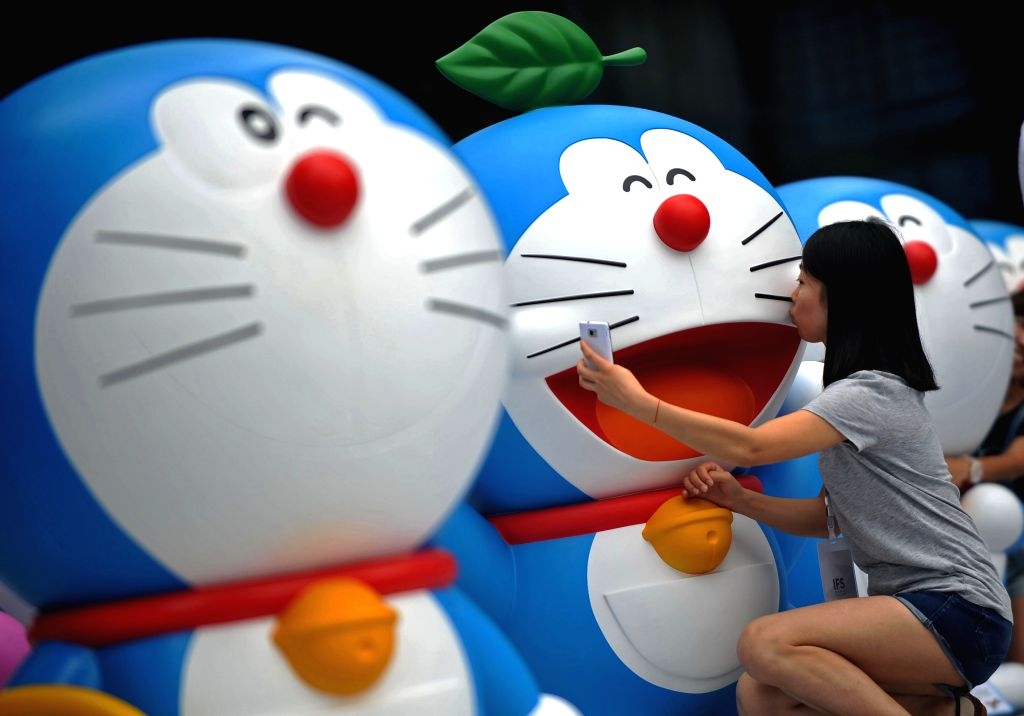 A visitor takes a selfie with a Doraemon figure during a Doraemon exhibition in Chengdu, capital of southwest China's Sichuan Province, Aug. 16, 2014. The ...