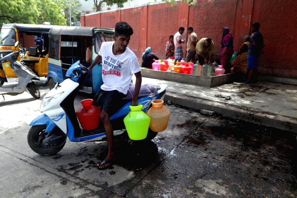 Chennai: A boy carries plastic vessels on his two-wheeler after collecting drinking water from a water distribution point amid ongoing water crisis in Chennai, on June 19, 2019. Chennai and several other places in Tamil Nadu are going through water c
