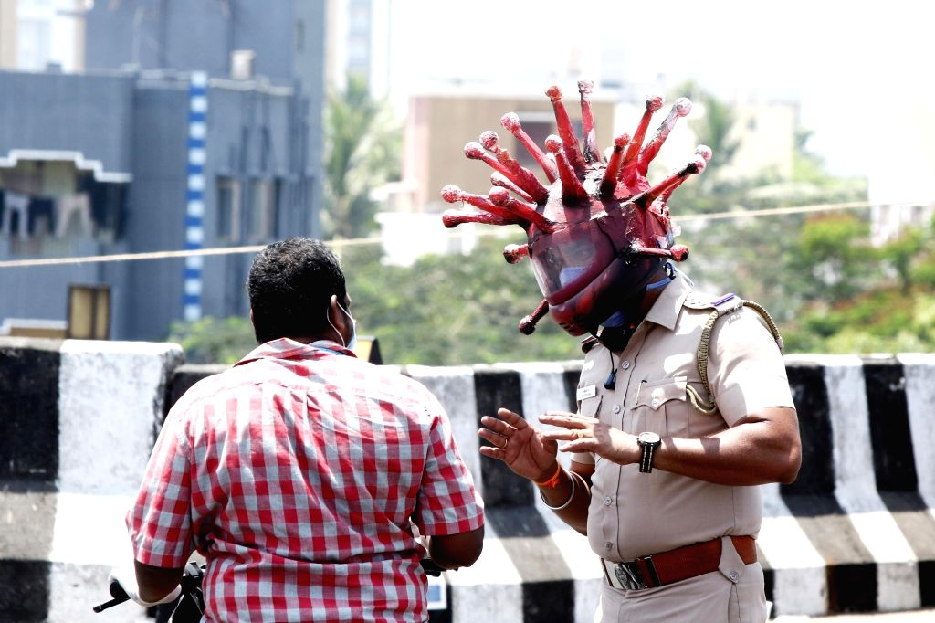 Chennai:  A Chennai cop wearing a 'Corona Helmet' intercepts a lockdown violater on March 29, 2020. The cop wearing the helmet, police Inspector Rajesh Babu in collaboration with a local artist Gowtham had come with this innovative initiative to diss - Gowtham