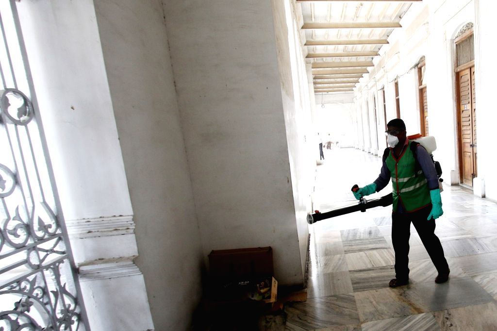 Chennai: A Municipal worker sprays disinfectant at the building premises of Chennai Municipal Corporation as a precautionary measure to contain COVID-19 amid coronavirus pandemic, in Chennai. (Photo: IANS)