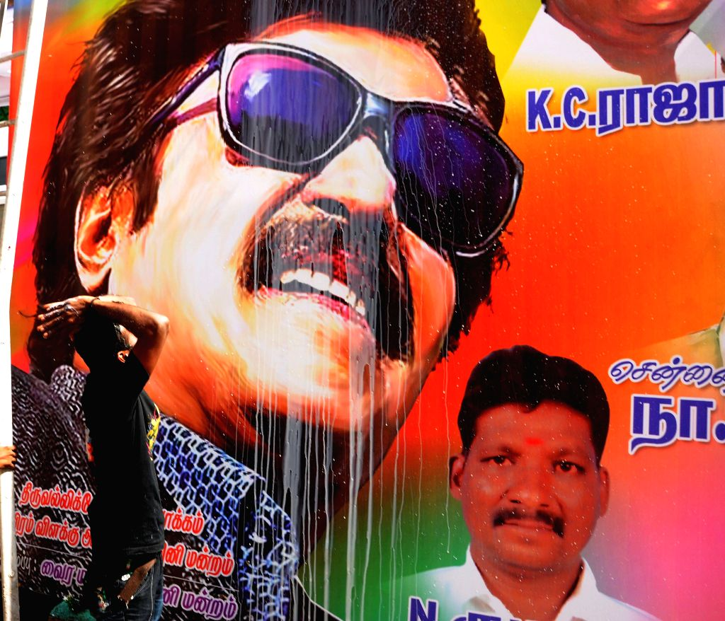A Rajinikanth fan pours milk on a poster of his newly launched film `Lingaa' on his birthday in Chennai on Dec 12, 2014.