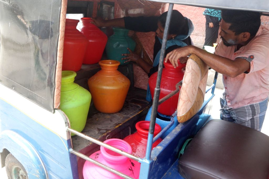 Chennai: A woman adjusts plastic vessels in an auto-rickshaw after collecting drinking water from a water distribution point amid ongoing water crisis in Chennai, on June 19, 2019. Chennai and several other places in Tamil Nadu are going through wate