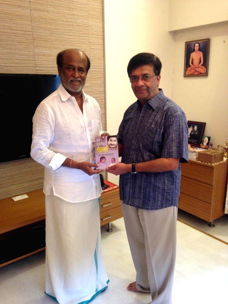 Dramatist Y. G. Mahendra calls on actor Rajinikanth to present him his book `Naan Suvasikkum Sivaji` in Chennai.