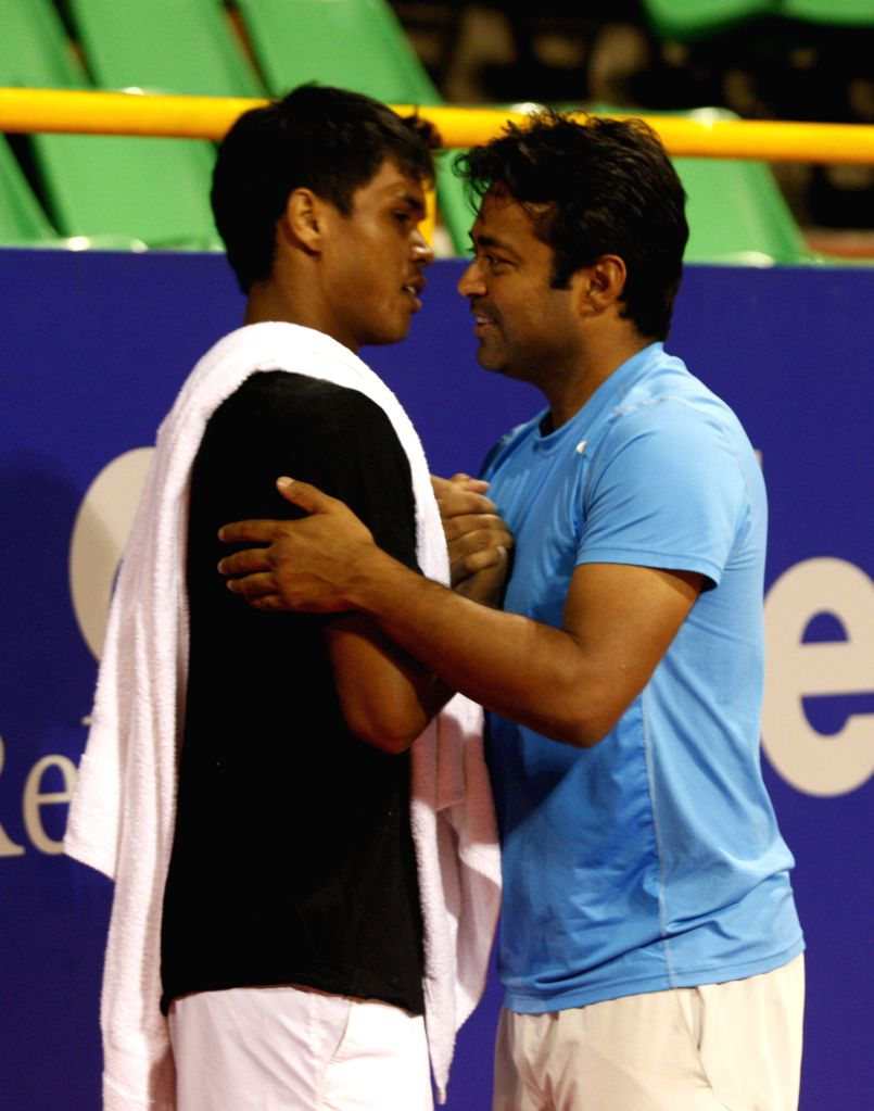 Indian Tennis player Leander Paes interacts with Indian Tennis player Somdev Devvarman during a practice session of ATP Chennai Open 2015 at SDAT Tennis Stadium in Chennai on Jan. 3, 2015.