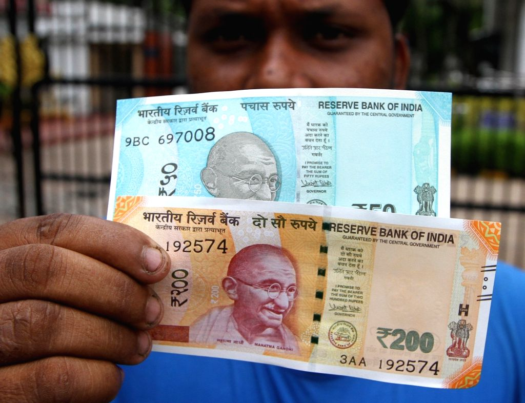 Chennai: People seen with the new 200 rupee and 50 rupee currency notes at the Reserve Bank of India in Chennai on Aug. 28, 2017. (Photo: IANS)