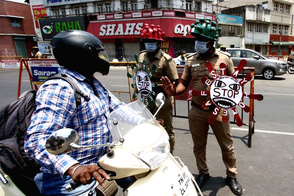 "Chennai: Police personnel wear 'Corona Helmets' and carry placards in the shape of coronavirus that read ""STOP"" to dissuade people from stepping out of their houses during the 21-day nationwide lockdown (that entered the 15th day) imposed as a precau"
