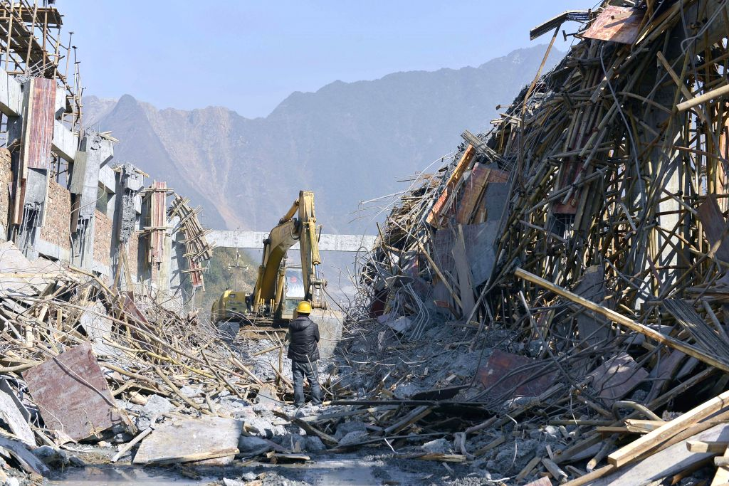 A worker stands on the ruins of a building site after a rooftop and scaffold collapsed in Chenzhou, central China's Hunan Province, Jan. 3, 2015. Five workers were .