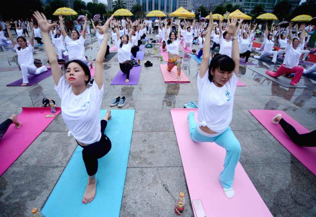 CHENZHOU, July 3, 2016 - Yoga enthusiasts perform yoga at the Wuling Square in Chenzhou, central China's Hunan Province, July 3, 2016.