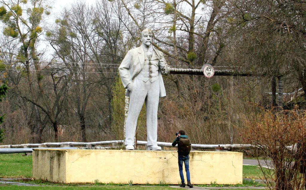 CHERNOBYL, April 8, 2017 - A man takes photos of a Lenin statue in Chernobyl, Ukraine, on April 5, 2017. The Ukrainian government has recently declared the territory around Chernobyl nuclear power ...